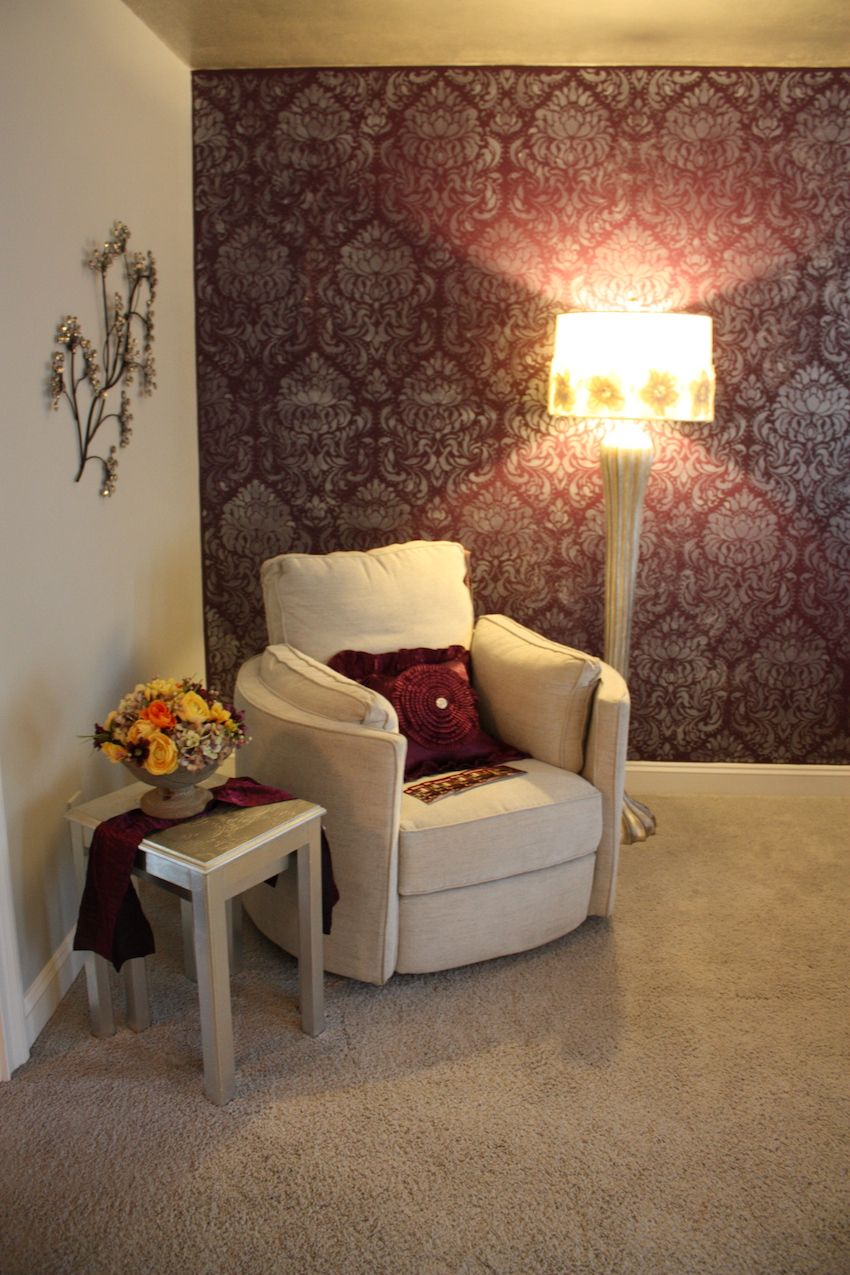 This versatile armchair grouping is accessorized with bits of bling on the pillows and the lamp. The embellished wall decor dresses up the plain wall but does not compete with the accent wall.
