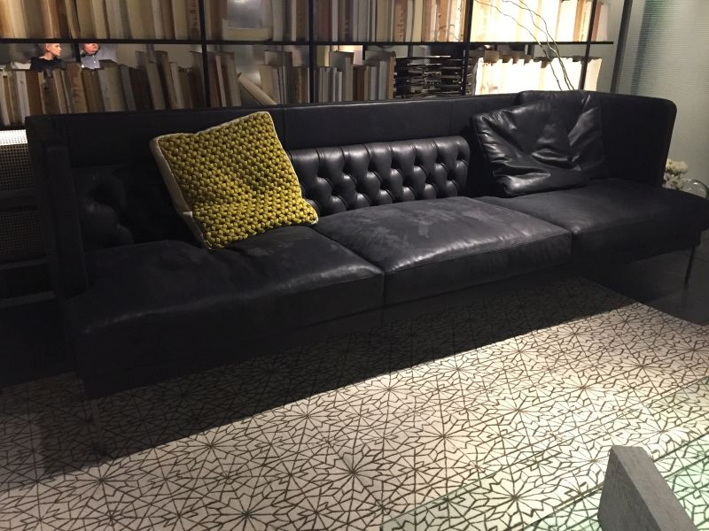 Black leather sofa with chartreuse crocheted pillow