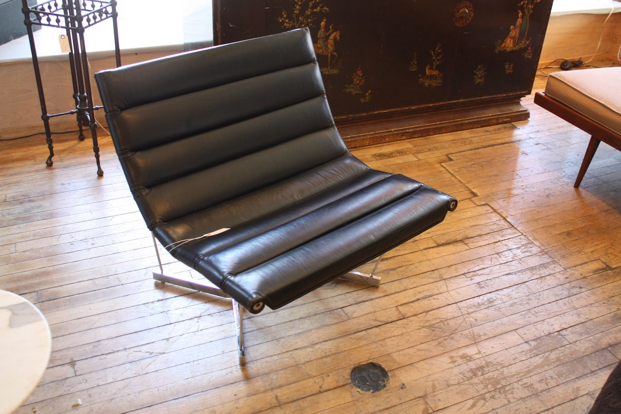 This is a classic George Nelson design -- the Catenary Leather Chair. Upholstered in black leather the set sit upon a chrome-plated steel base.