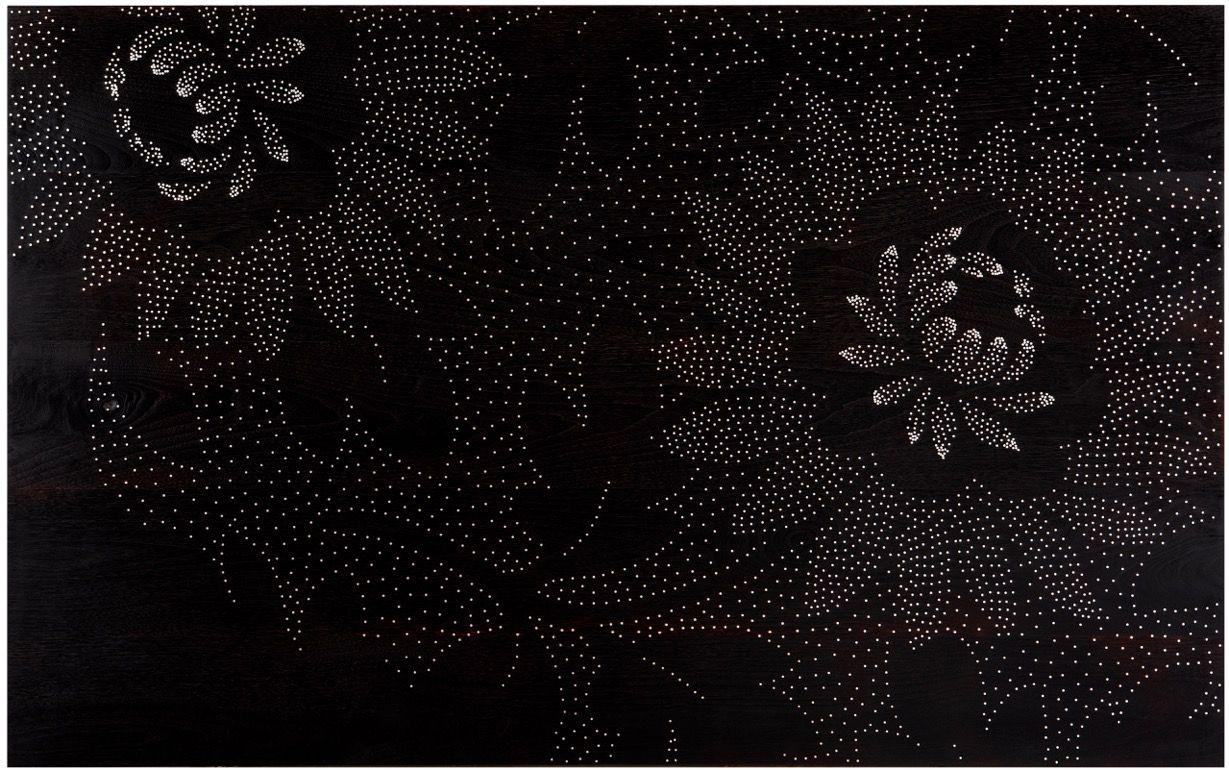Detail of a floral motif on dark wedge wood.