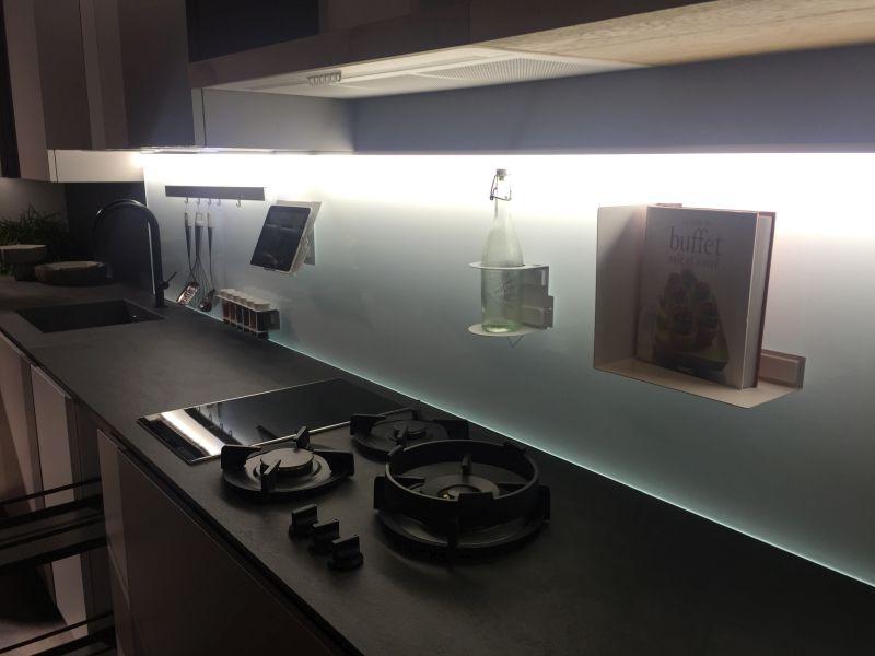 Glass backsplash with light and black countertop