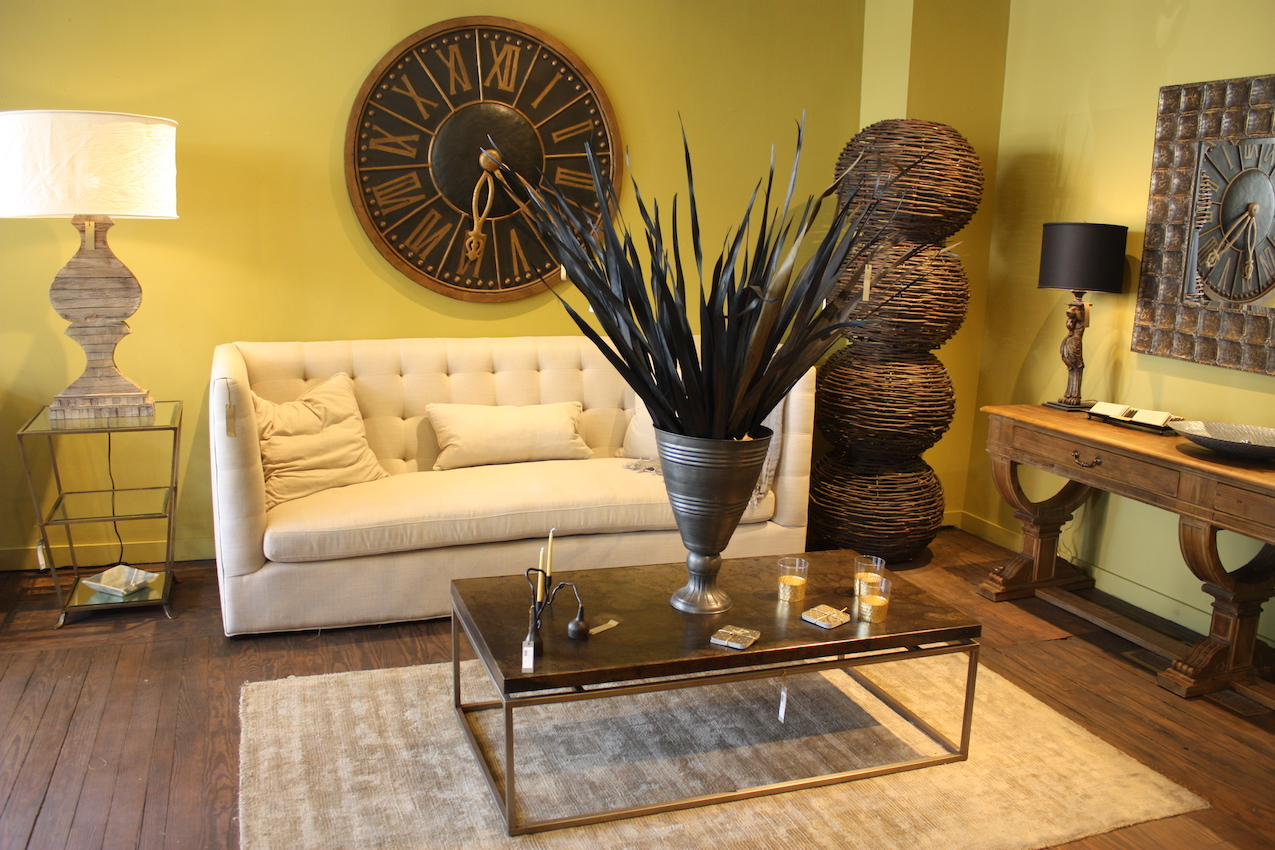 Here's an artful living room grouping that features a very versatile tufted sofa and clean-lined coffee table. The table lamps is especially interesting because while it looks like a substantial layered wood base, it;s actually only an inch or two thick when viewed from the side.