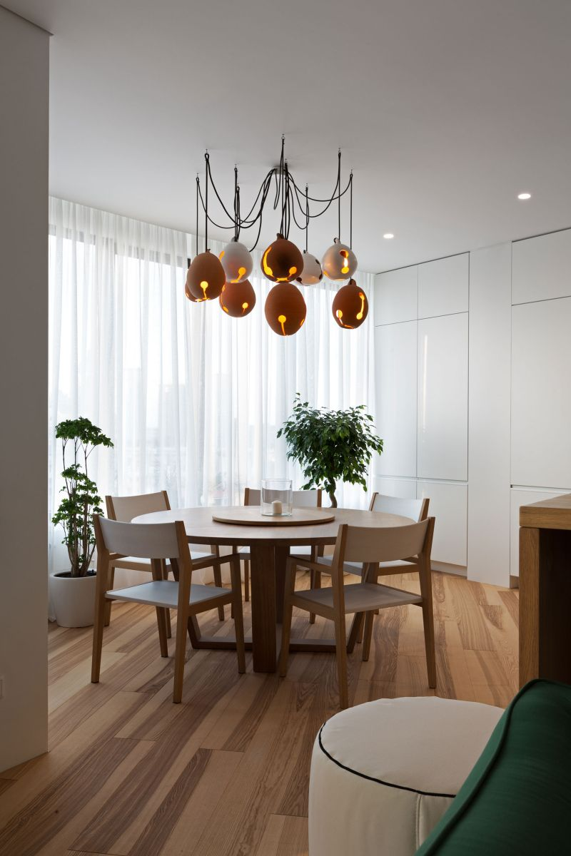 Minimalist apartment decorated with shades of forest green minimalist apartment in kiev dining area chandelier mozeypictures Images