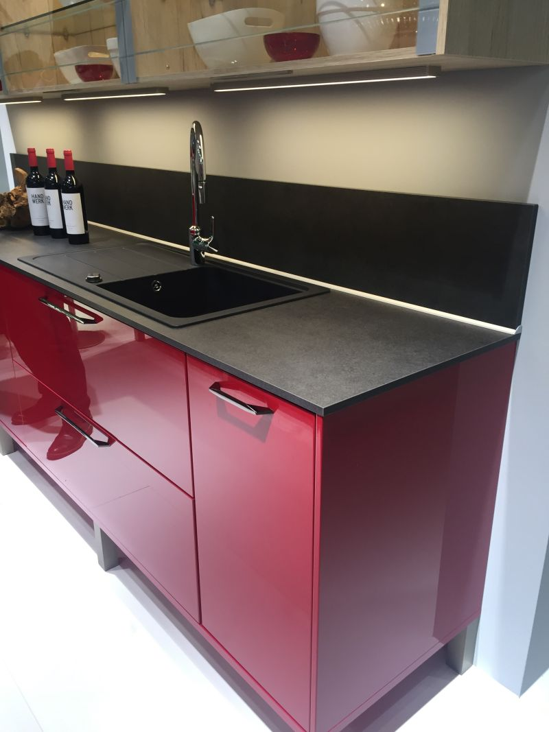 Red lower kitchen cabinets with grey composit and backsplash
