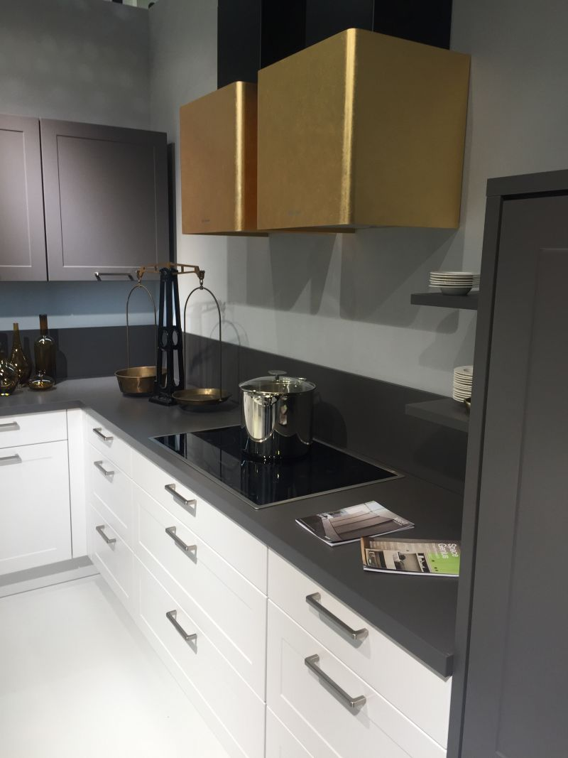 White cupboards with gray shade and gold copper hood
