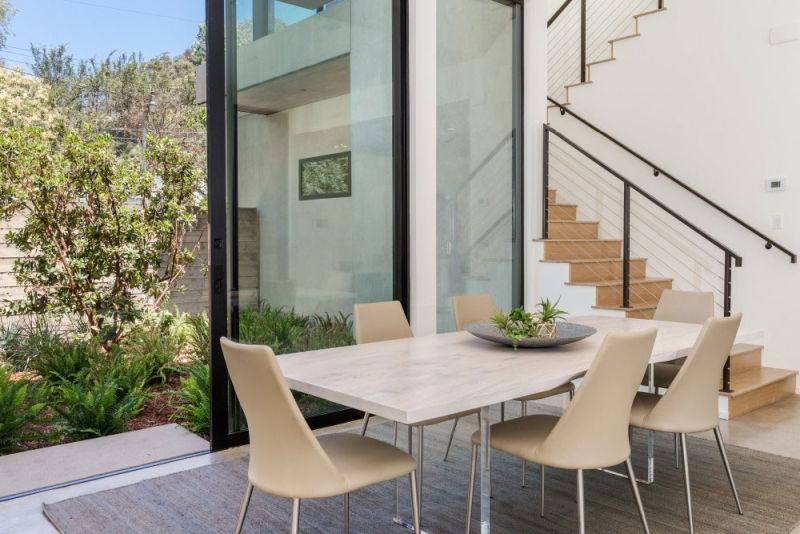 Contemporary home in Californian hillside dining table by staircase