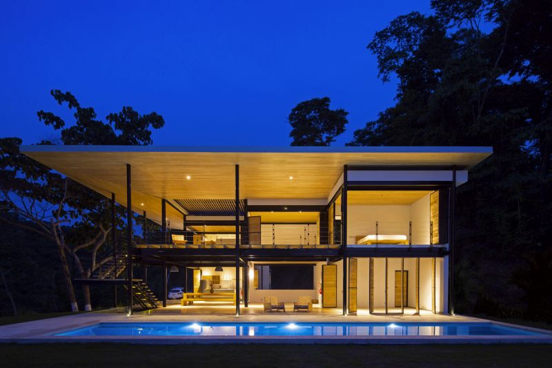 House between the ocean and the jungle lights at night