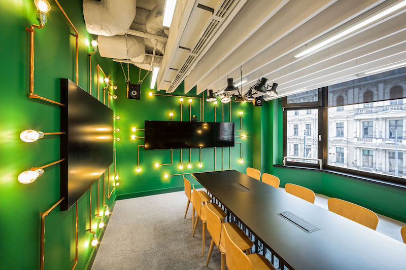 Opera office meeting room with green walls and pipe lighting