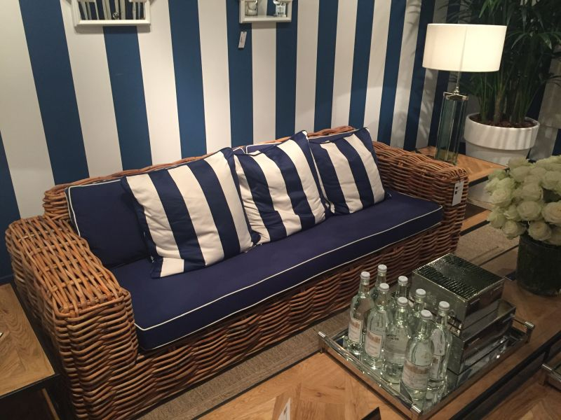 rattan-outdoor-couch-with-striped-blue-and-white-pillows