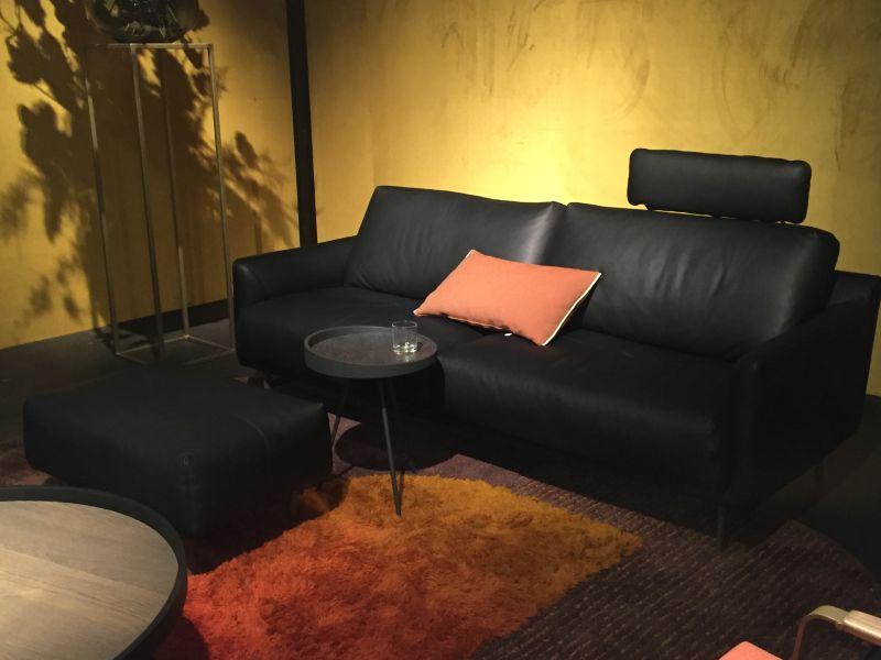 Black leather sofa with orange pillow