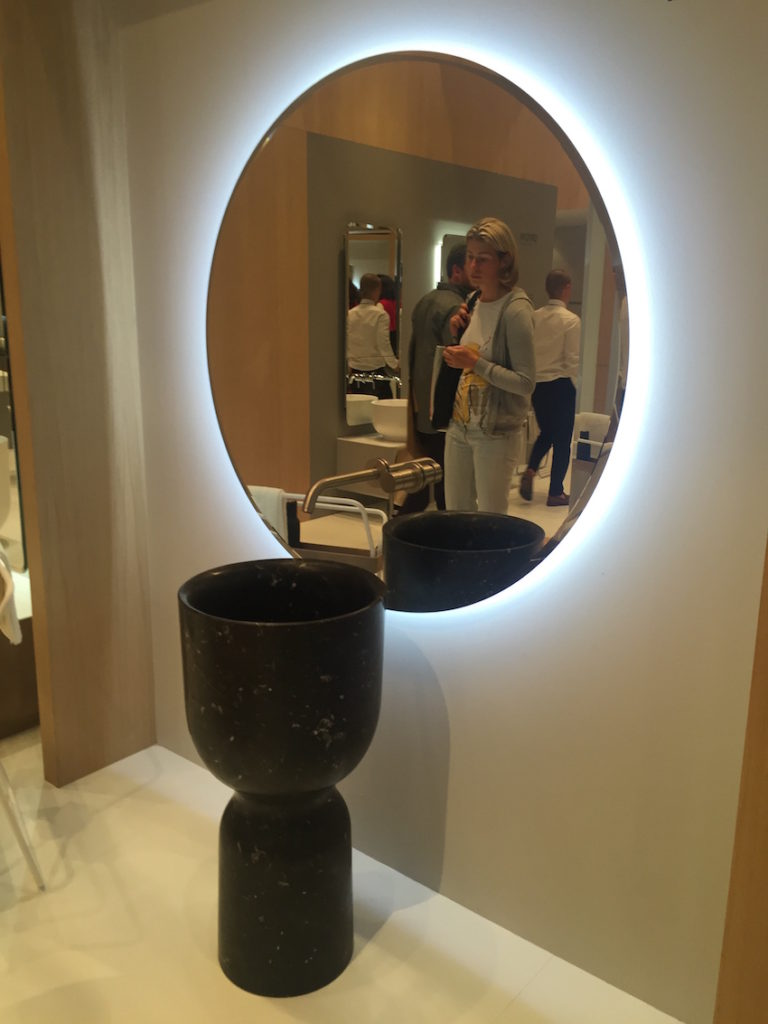 A modern black stone pedestal sink paired with a large lighted mirror is stunning.
