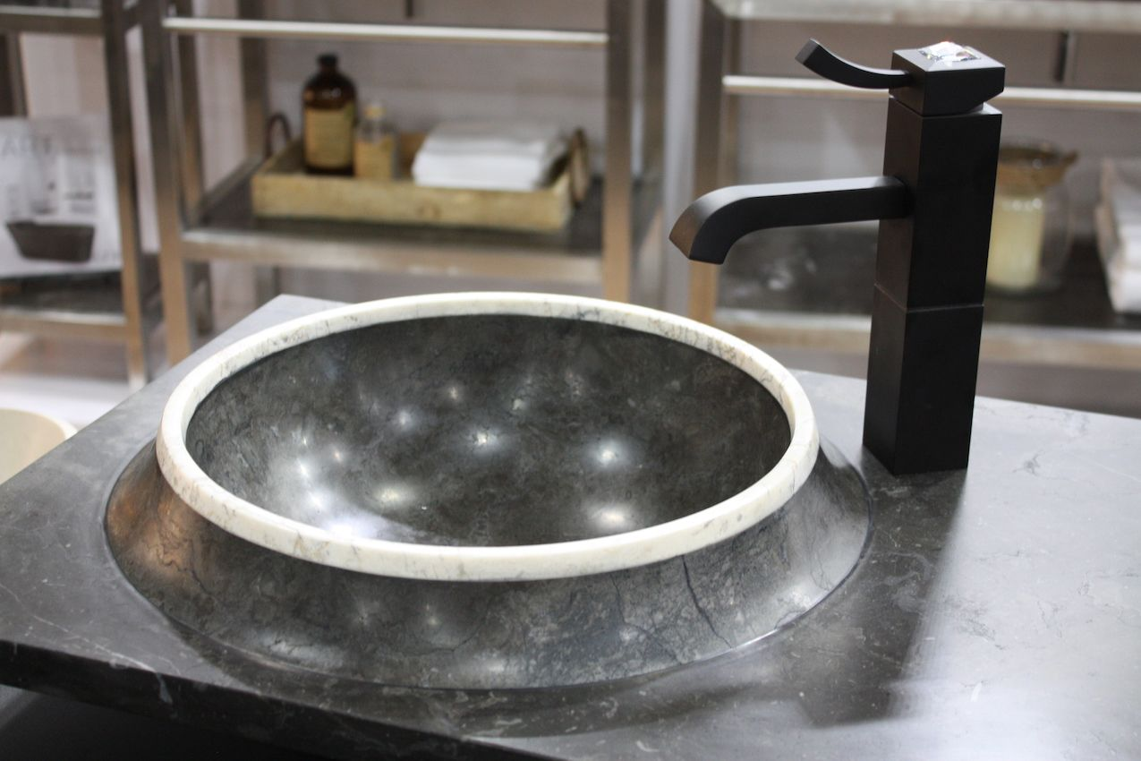 The unusual sink includes a contrasting stone rim.