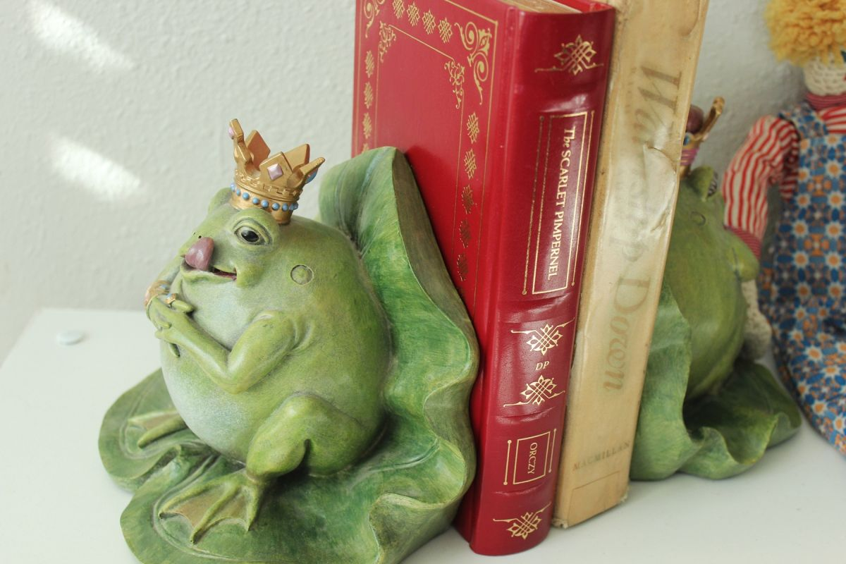 oversized frog bookends holding
