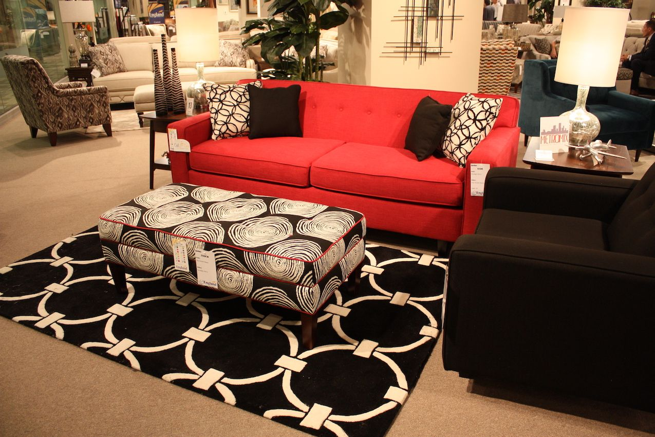 The only additionalred accent in this room is the red piping on the upholstered ottoman.