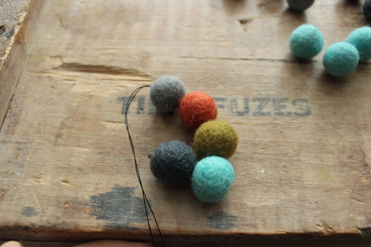 add two more felt balls onto your thread