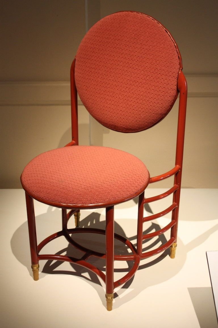 The unique chair is made of enamel, brass and upholstery.