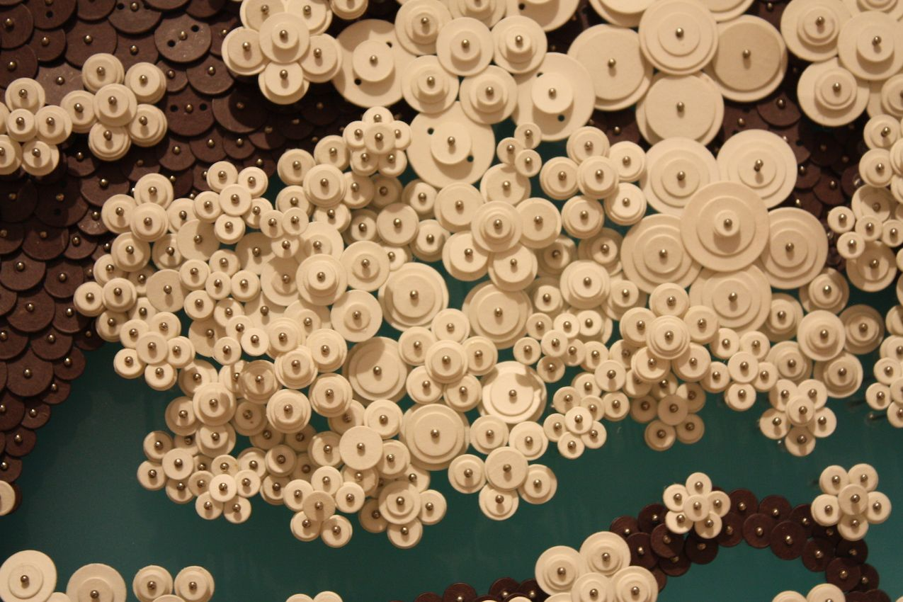 Paper buttons of many sizes are used to create texture and dimension.