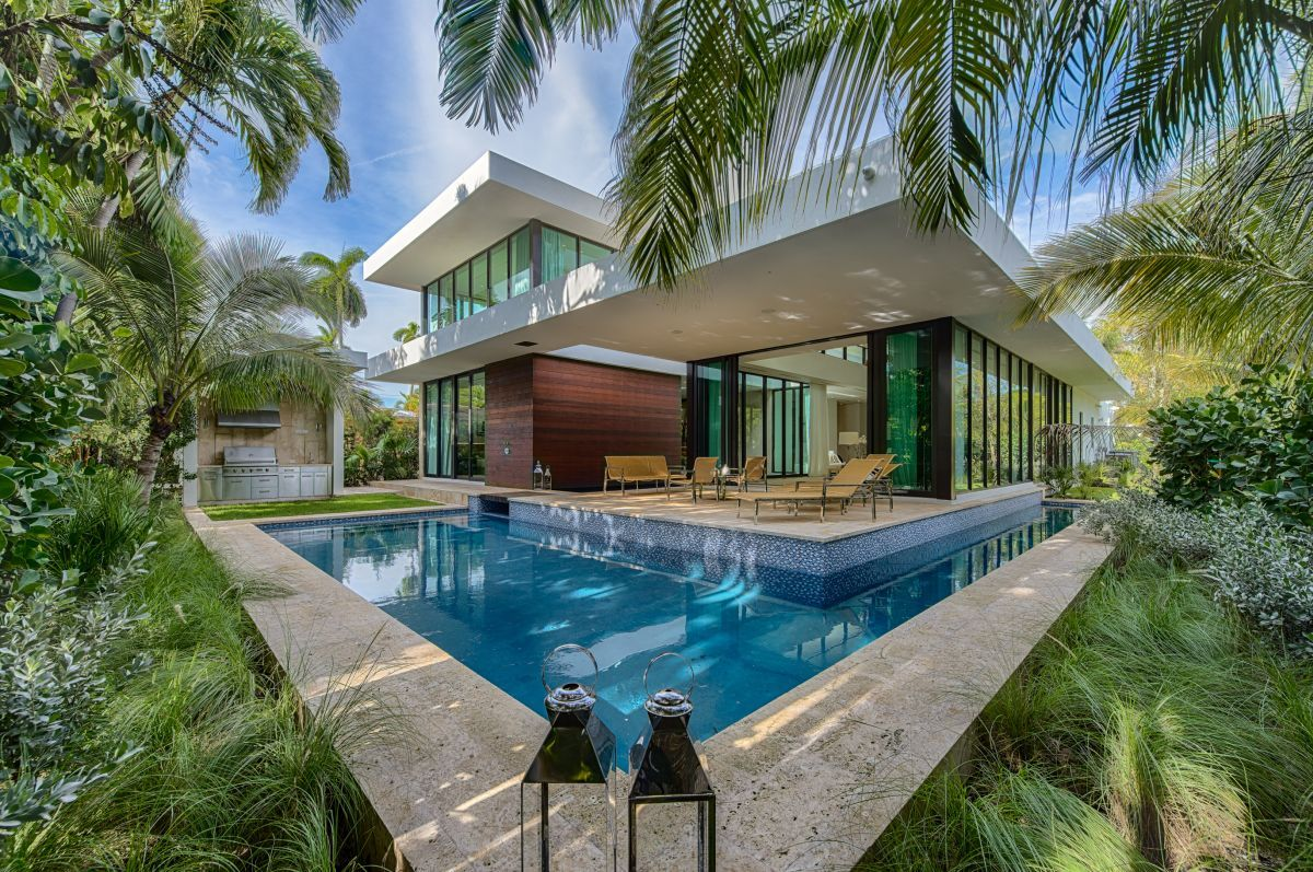 The house has an L-shaped pool that wraps around it, making it appear to be floating