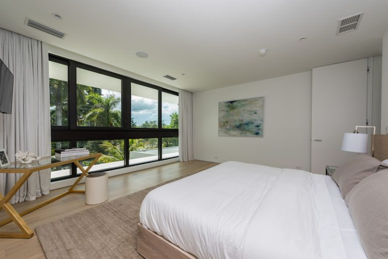 The master bedroom is a large and bright space with long curtains and an overall neutral decor