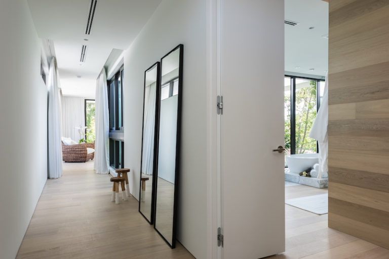 To make the hallway appear less narrow, a pair of framed mirrors was added