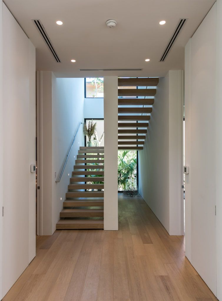 A set of floating wooden stairs connect the two floors and overlook the garden through large windows