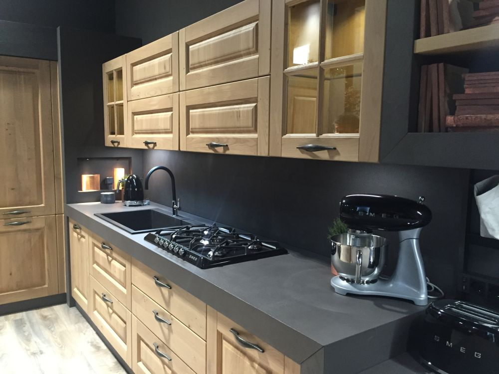 Natural wood molded kitchen cabinets with black counter top
