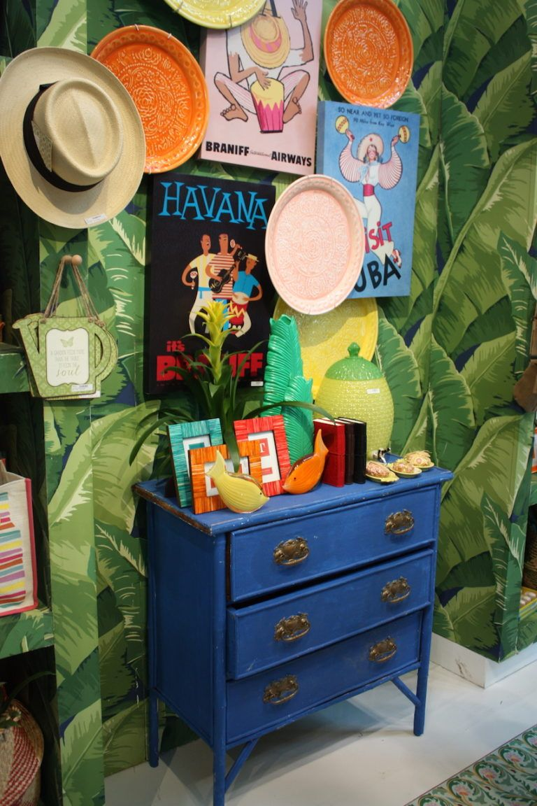 The dresser is mixed with other vibrant accessories and a boldly patterned wallpaper.