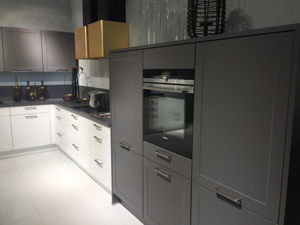 White and grey kitchen cabinets with a strong gold hood
