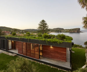 A Green, Prefabricated Home With A Living Room And Water Views
