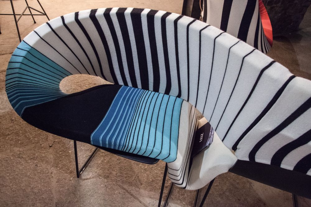 The seat and backrest are sinuously connected, forming a continuous and fluid form