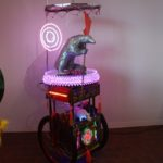 The eclectic mix of neon, plastic figures and a wheeled base are intriguing.