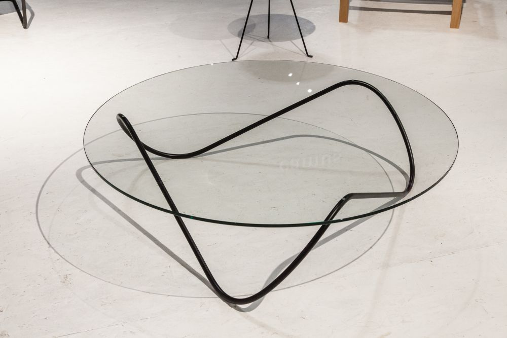 The sleek, fluid base of this table touches the glass top and the floor in three points, being perfectly balanced