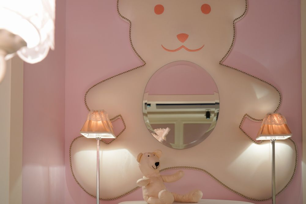 Everything can be customized to look cute in a nursery room, like this mirror framed by a giant teddy bear