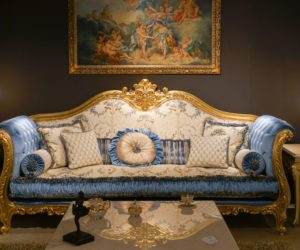 rococo blue sofa with gold frame - and coffee table with a baroque design - framed wall art above sofa