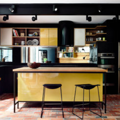 Black kitchen yellow cabinets brick floor