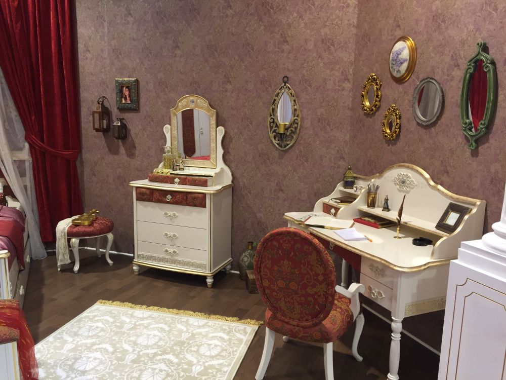 A classic writing desk with a decorative golden rim and soft and delicate curves fits perfectly in a girl's room