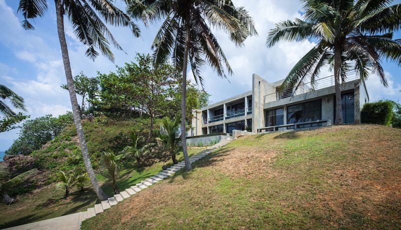 Cliff Villa In Thailand Framed By Coconut Trees And Views Of The Sea