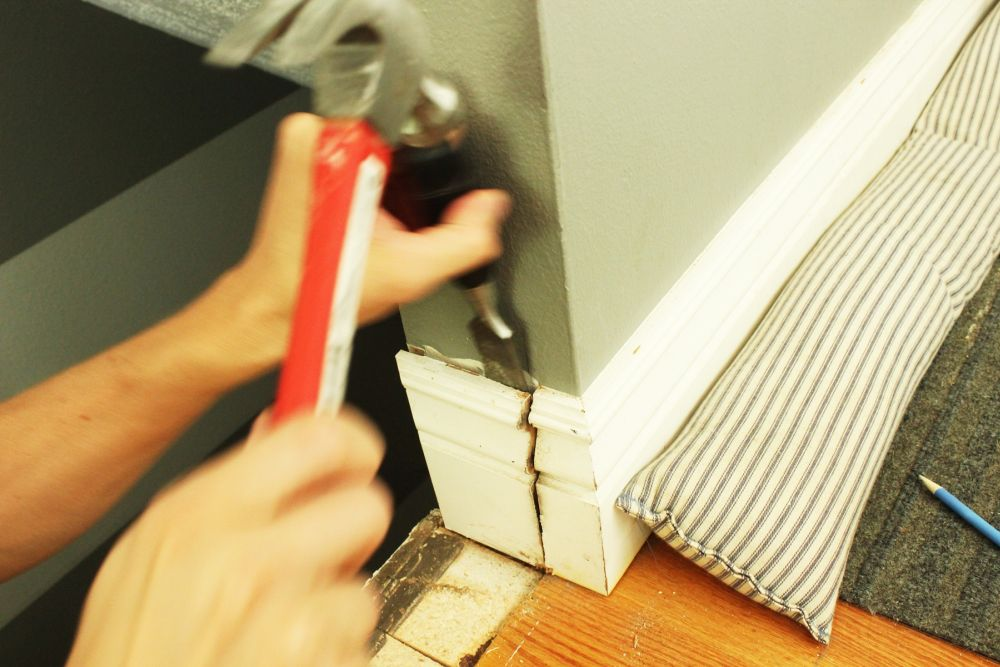 A file or chisel and hammer should remove the baseboard chunk pretty easily.