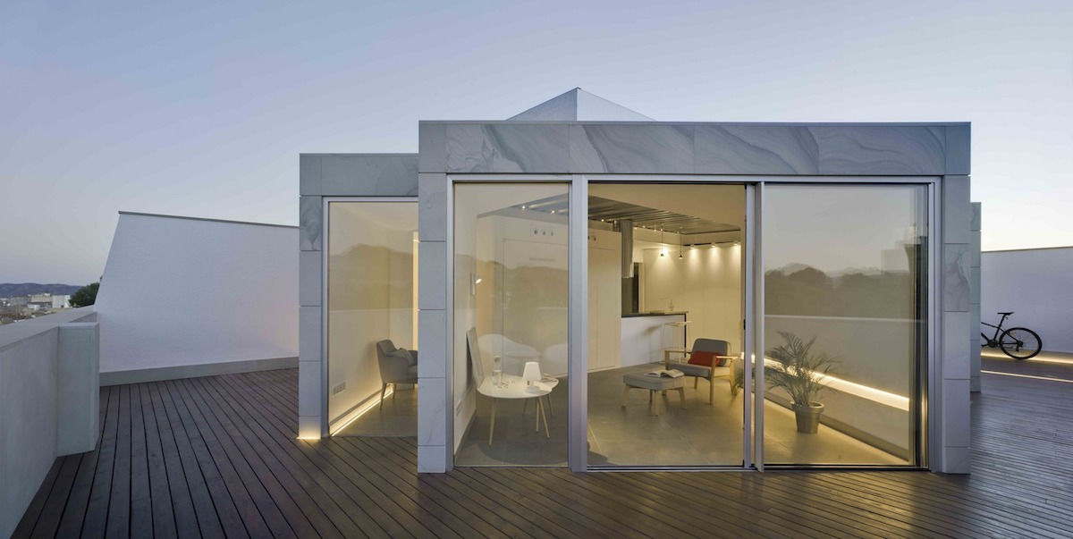 Large sliding glass doors link the interior spaces to the wooden roof terrace