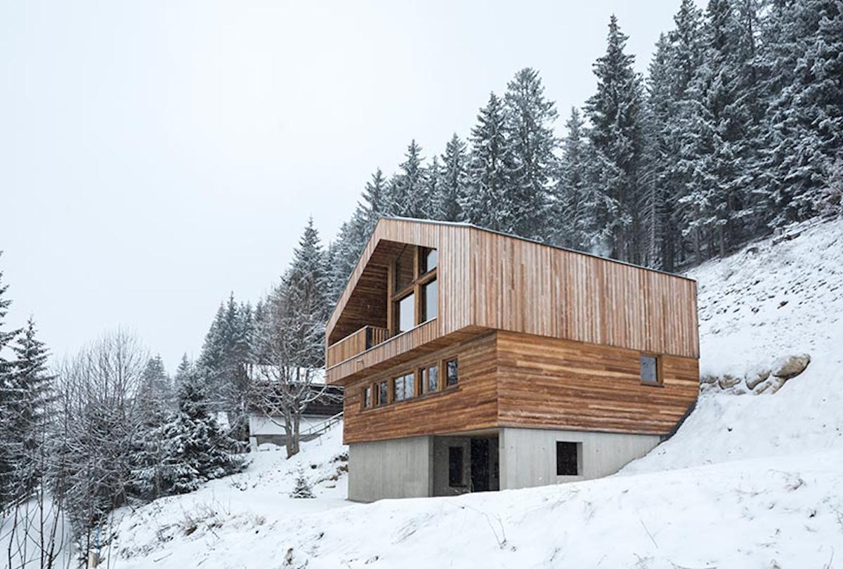The house sits on a slope in the French Alpa, being surrounded by trees
