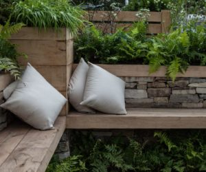 Corner garden bench made from stacked rocks and wood slabs