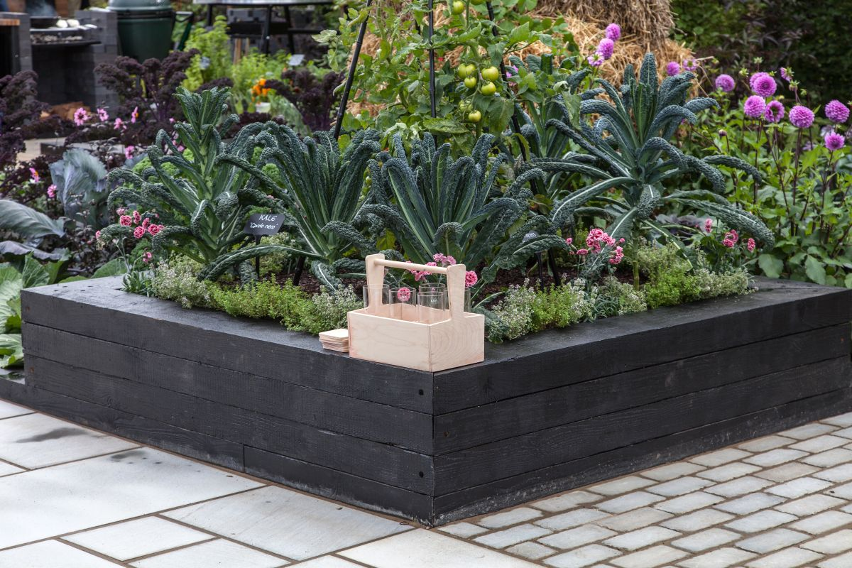 The wide rim of a large garden planter can double as a bench