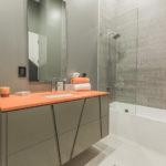 Gray walls and pop of orange through vanity countertop