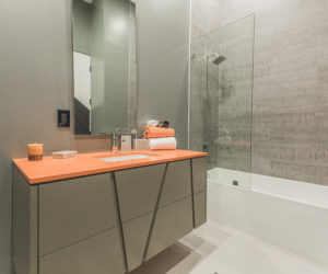 Gray walls and pop of orange through vanity countertop