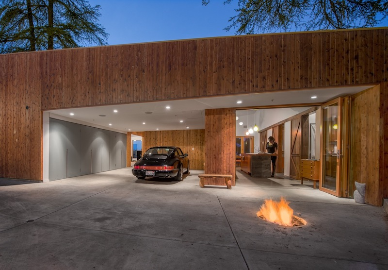 The covered parking area and a roofed terrace serve as transitional spaces between indoor and outdoor