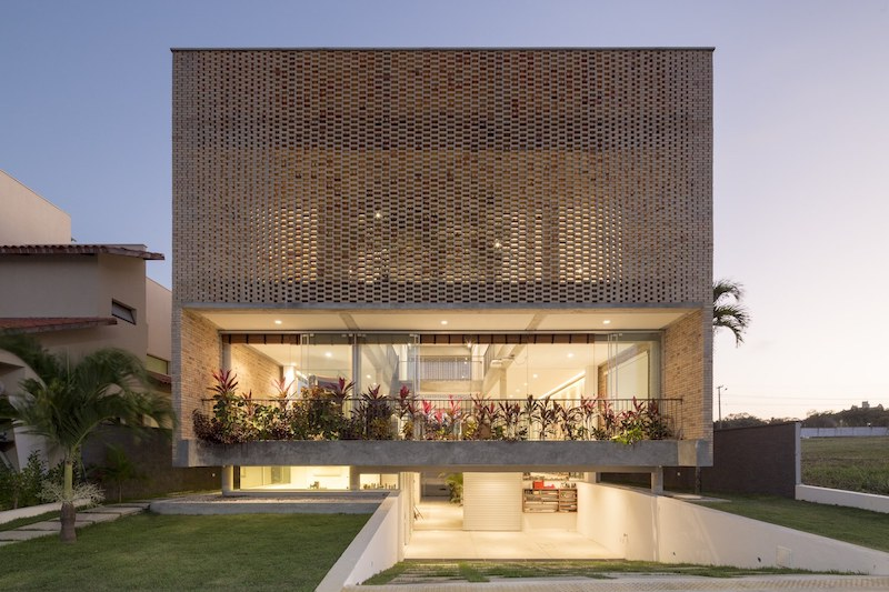 The perforated facade allows light to enter the house but at the same time offers less privacy than a fully solid facade