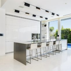 Large contemporary white kitchen design with island and black ceiling lighting fixtures