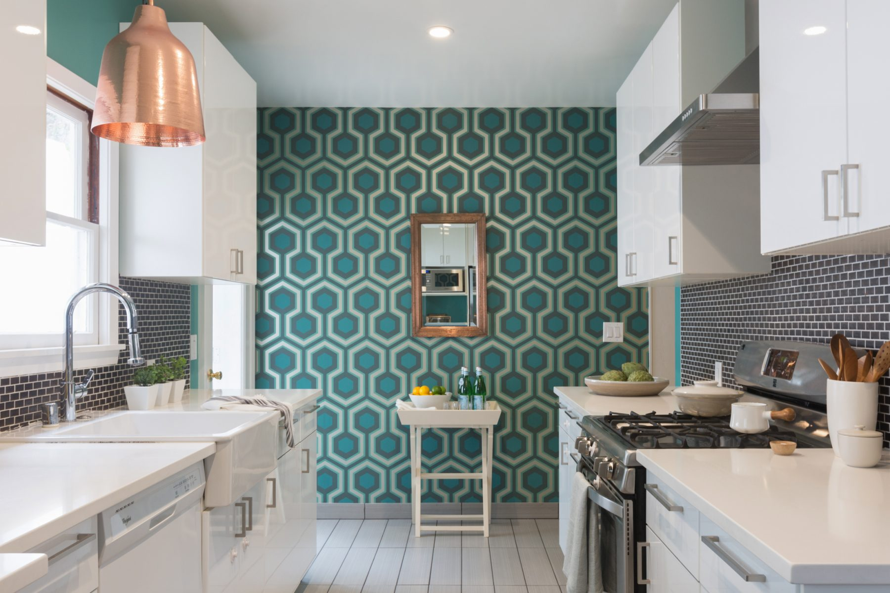 Teal wallpaper at the end of a kitchen.