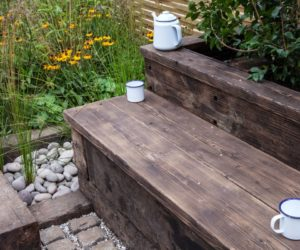 Reclaimed wood bench seating around flowers