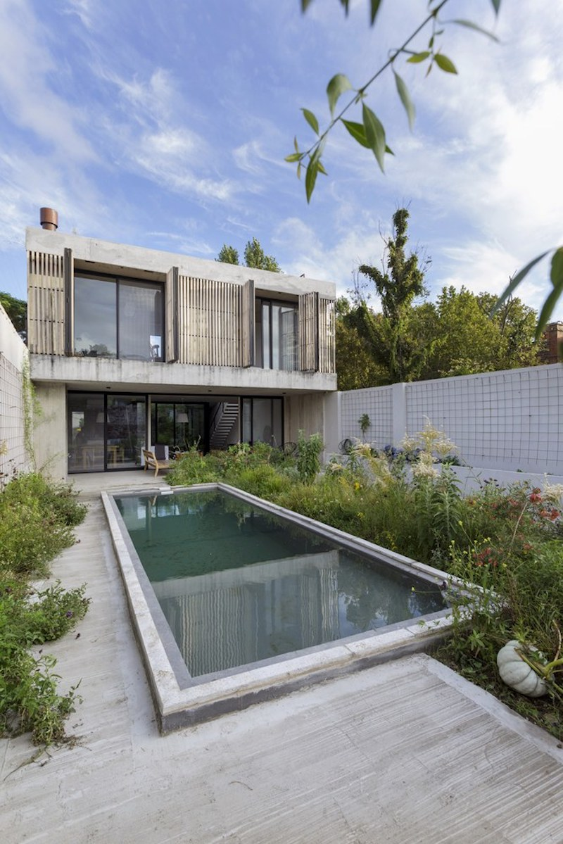 ... The Swimming Pool Is Positioned At The Center Of The Yard, With  Greenery Growing Around
